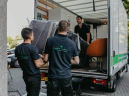 Drie verhuizers die meubels een een vrachtwagen laden voor meubeltransport.